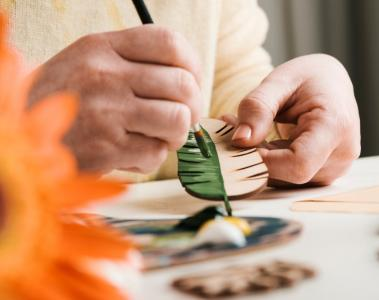 picture of someone painting a wooden leaf
