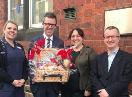 picture of Woodcock Haworth & Nuttall staff donating a hamper raffle prize to Hospice @ Home nurse Donna