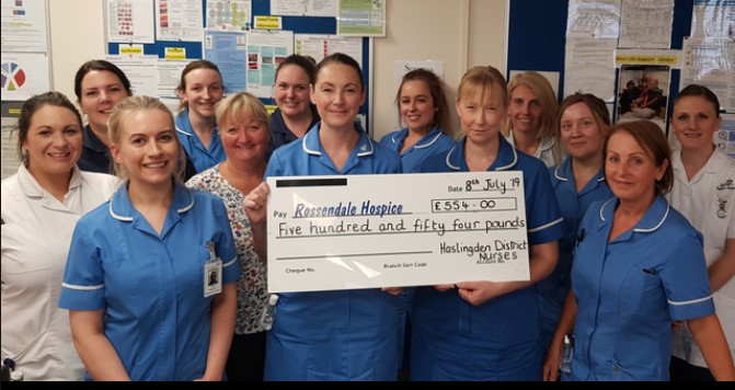 Haslingden District nurses photo holding cheque donation
